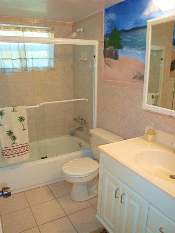 Full second bath with beach and ocean mural keeps the Florid