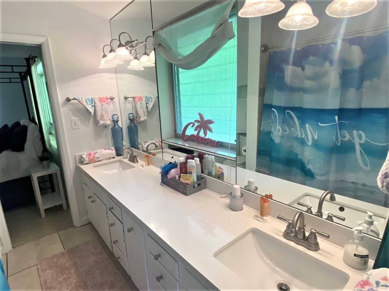 Jack and Jill bathroom has tub/shower combo.