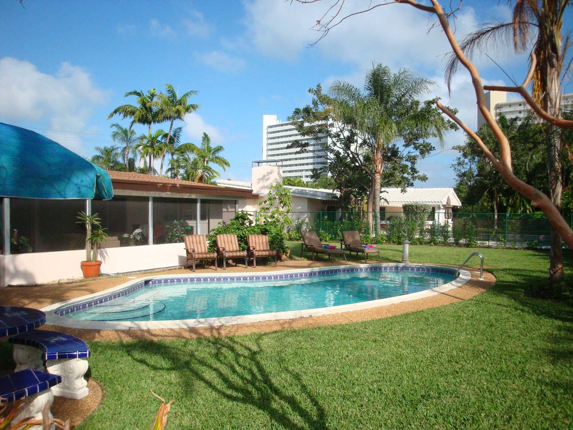 Pool area is surrounded by lush landscaping.