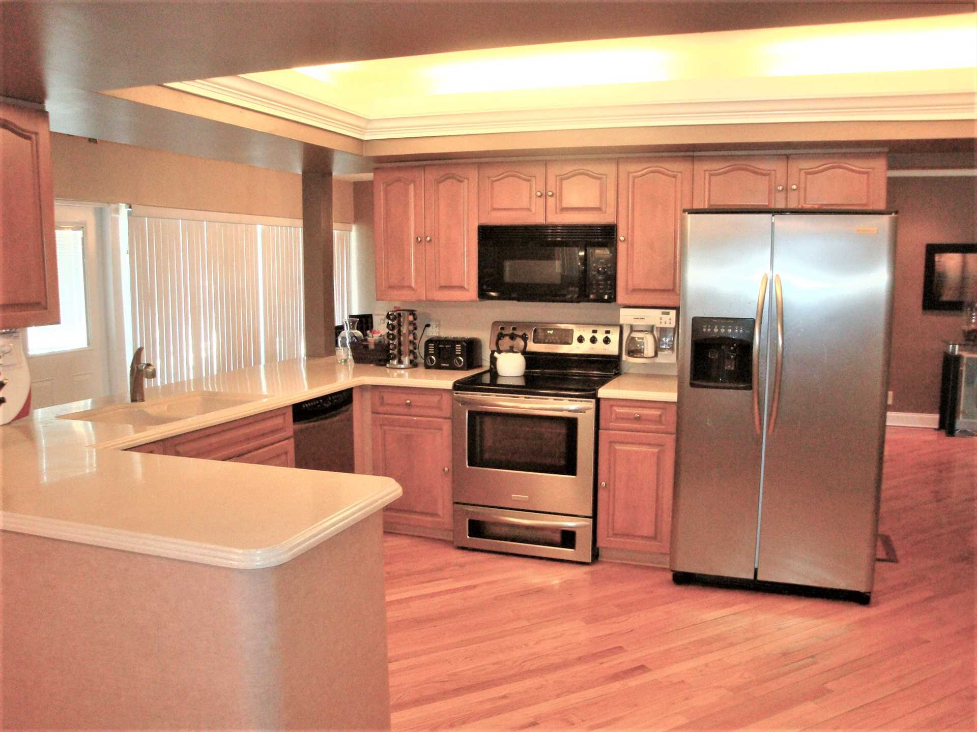 Open kitchen has all stainless appliances and solid wood cab