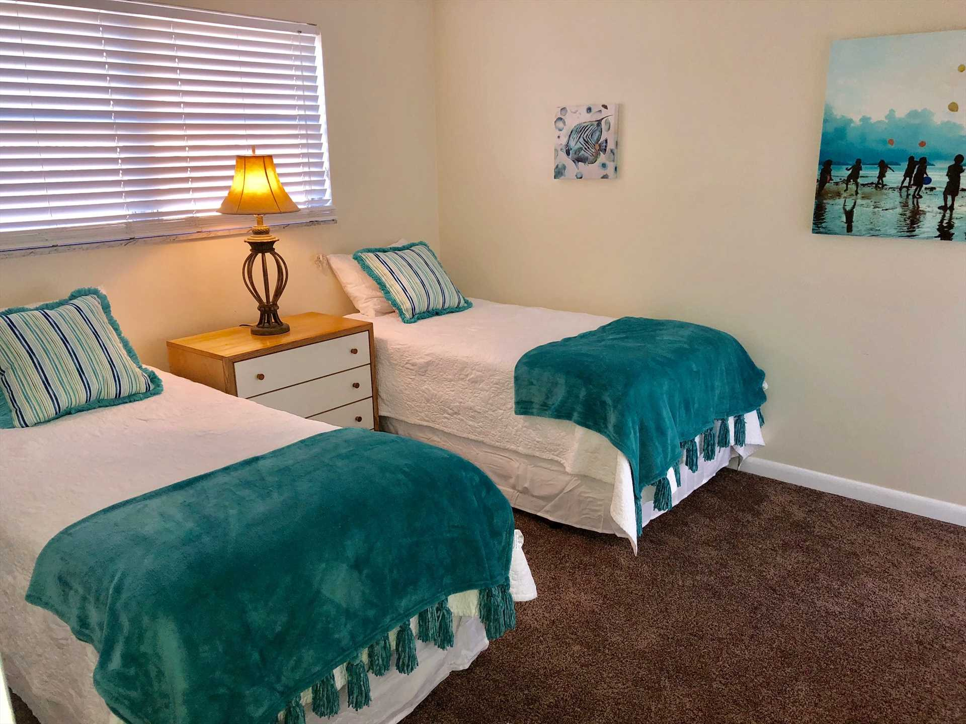 Brightly decorated twin bedroom has HDTV.