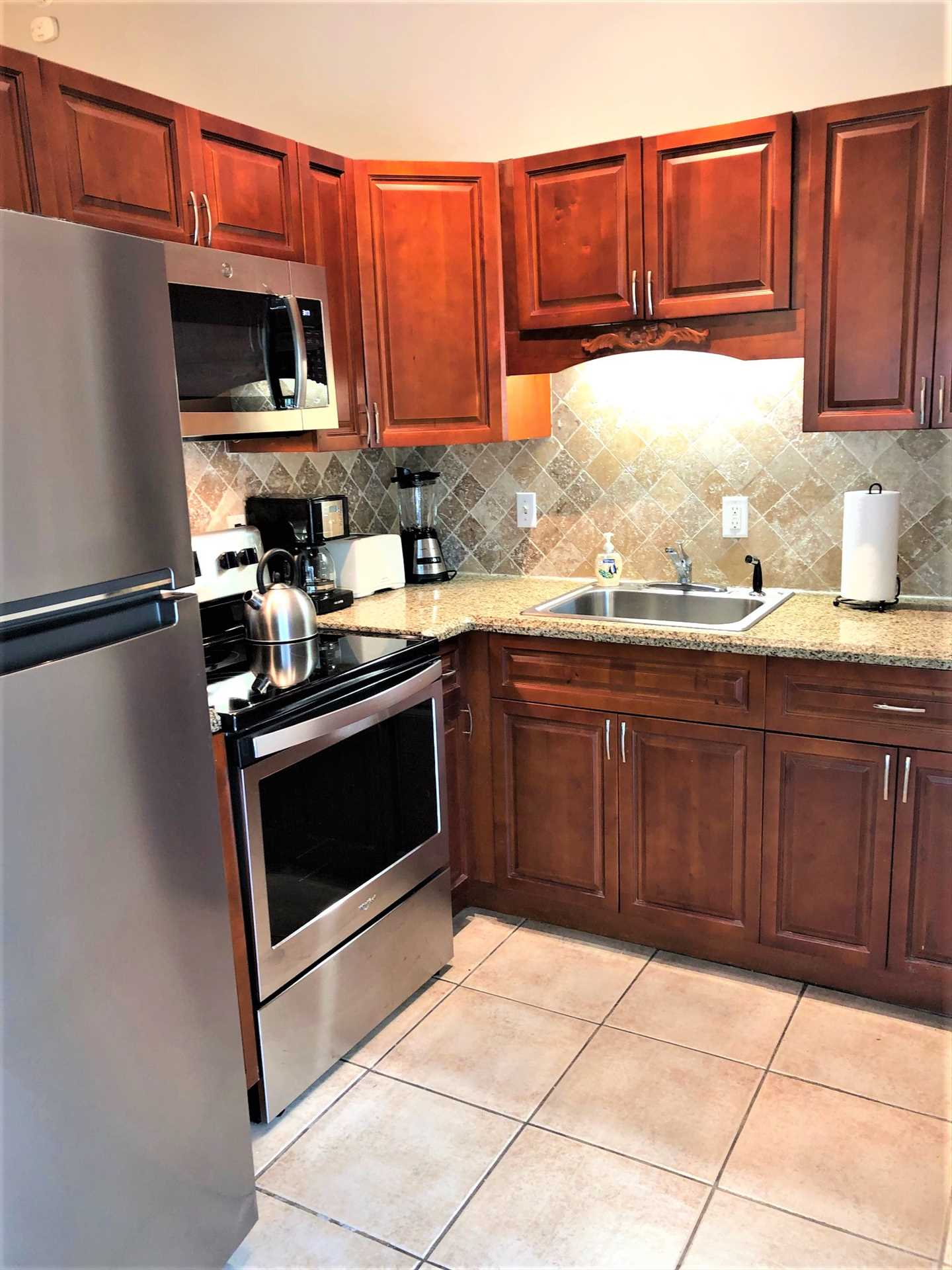 Galley kitchen features all stainless appliances.