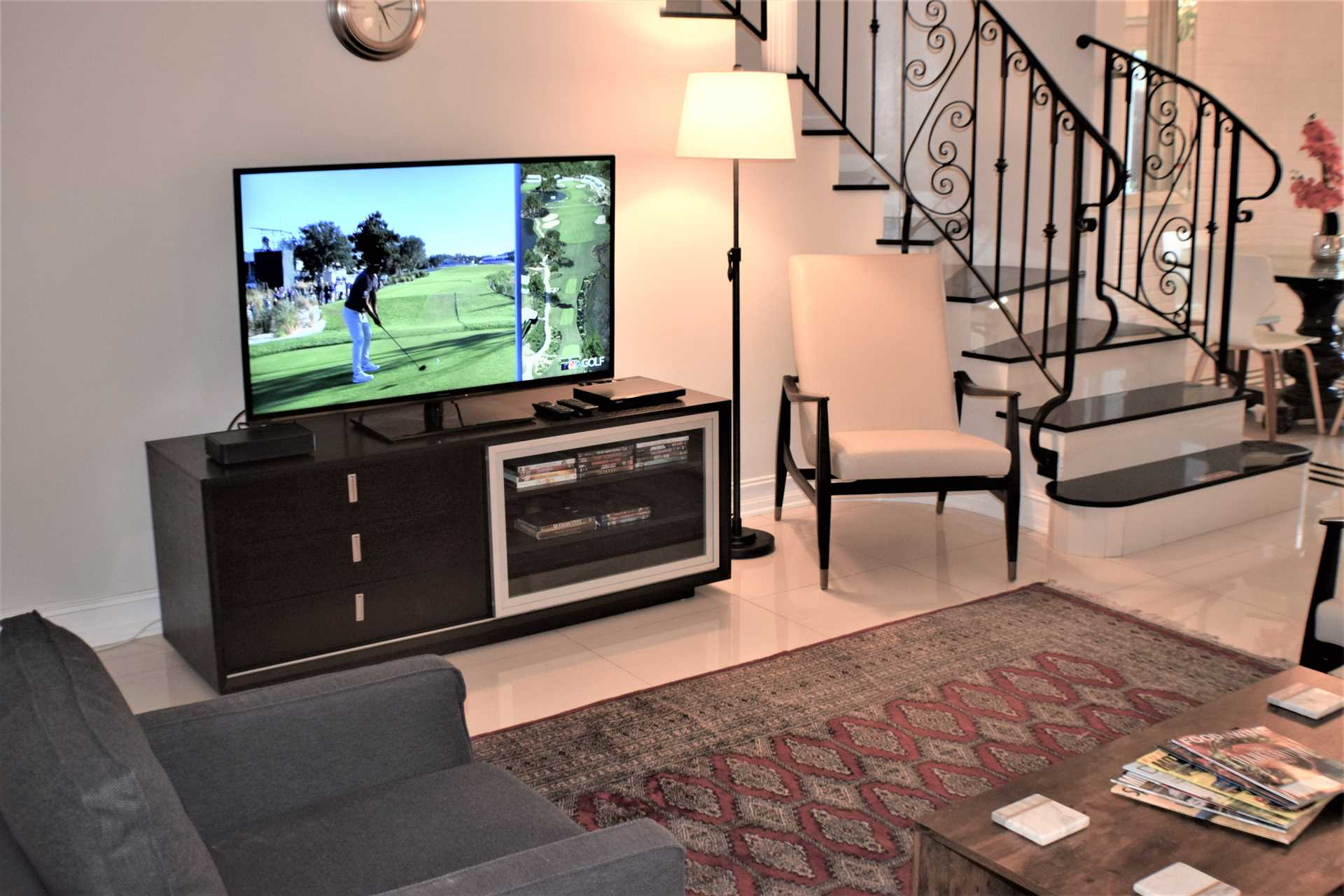 """Living room features a 65"""" HDTV with DVD player and lib"""