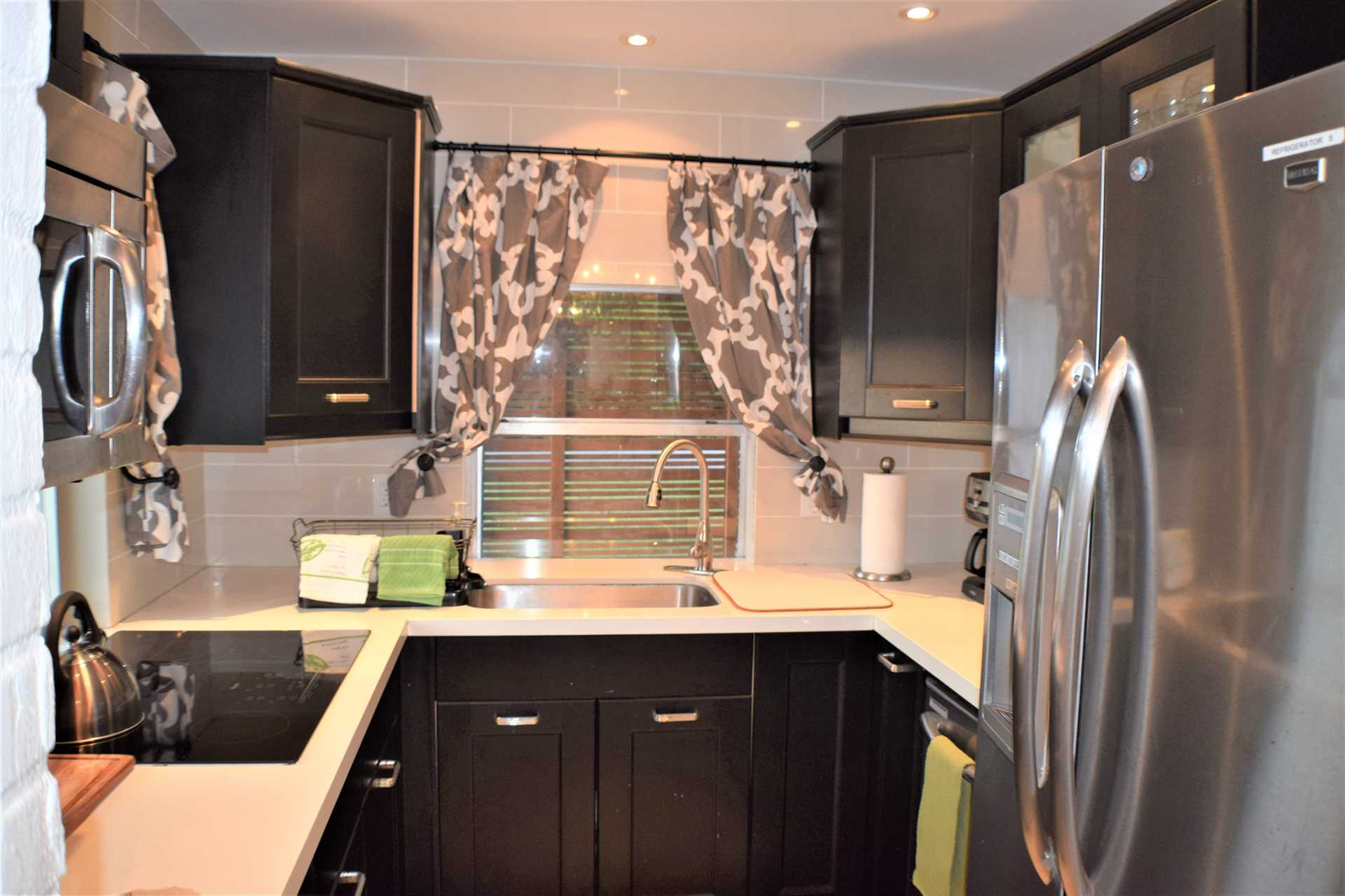 Galley kitchen has all stainless appliances.