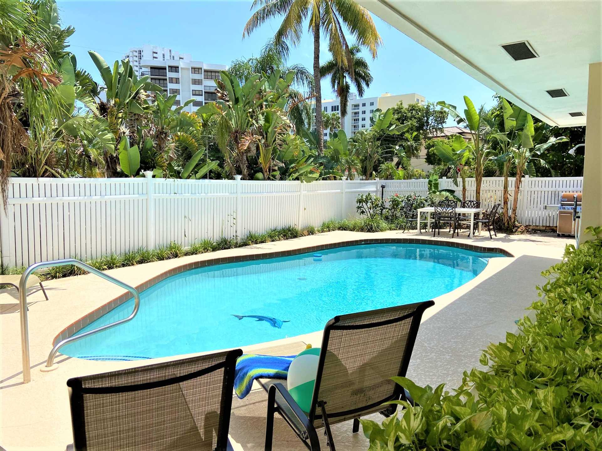 Pool deck is surrounded by a privacy fence.